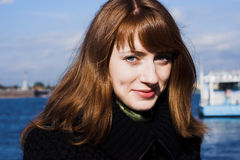 Redhead woman. Portrait of a young redhead woman standing by a river in St. Petersburg, Russia stock photography