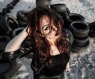 Redhead woman at the background of an old tires Stock Photos