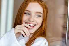 Redhead woman in bathrobe looking away Royalty Free Stock Images
