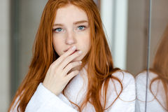 Redhead woman in bathrobe looking at camera Royalty Free Stock Photography