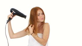 Redhead woman in bathroom drying hair with blow stock footage