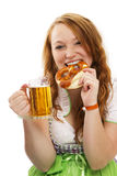 Redhead woman in bavarian dress with beer eating p Stock Photo