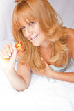 Redhead Woman In Bed with flowers Royalty Free Stock Image