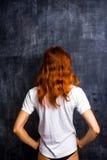 Redhead woman by blank blackboard. Redhead woman standing by blank blackboard Stock Photography