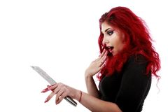 Redhead woman with a bloody hatchet in hand Stock Photos