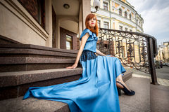 Redhead woman in blue dress posing on stairs at old building Royalty Free Stock Image