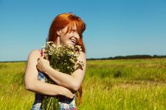 Redhead woman with a bouquet of flowers in a dress outdoors. stylish romantic young girl in field stock photo