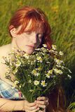 Redhead woman with a bouquet of flowers in a dress outdoors. stylish romantic young girl in field royalty free stock photography