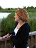 Redhead woman on bridge. Looking out over pond; scene is peaceful and calm Royalty Free Stock Photos