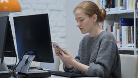 Redhead woman browsing internet online on smartphone stock video