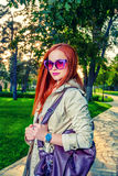 Redhead woman in casual clothing posing outdoors in 60th fashion  sunglasses and bright violet handbag Royalty Free Stock Photos
