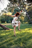 Redhead woman dancing in heels. And floral dress royalty free stock photo