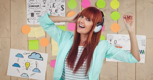 Redhead woman dancing while listening to music on headphones against graphics Royalty Free Stock Images