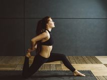 Redhead woman doing kneeling quad stretch. Photo of a beautiful young woman doing a kneeling quad stretch royalty free stock image