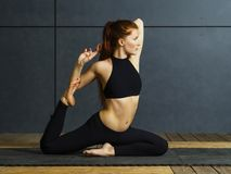 Redhead woman doing yoga stretches. Photo of a beautiful young woman doing yoga stretches royalty free stock photo