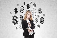 Redhead woman and dollar sign on concrete wall Stock Photos