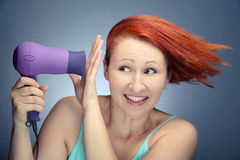 Redhead woman drying her hair Stock Photography