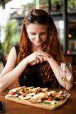 Redhead woman eating and drinking wine in restaurant royalty free stock image