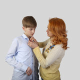 Redhead woman fastens teenage boy shirt Stock Photography