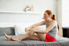 Redhead Woman Feeling Pain Waxing Her Legs. Young woman sitting on bed, doing routine leg waxing. The redhead girl bites a hairbrush to stand the pain while she Stock Photo