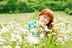 Redhead woman   in field of daisies Stock Photography
