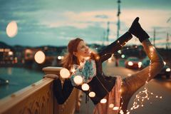 Redhead woman with garland fairy lights doing yoga vintage style stock photo