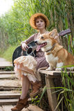 Redhead woman with guitar and corgi dog in countryside Stock Images