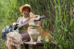 Redhead woman with guitar and corgi dog in countryside Stock Image