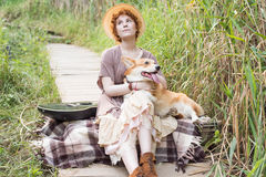 Redhead woman with guitar and corgi dog in countryside Stock Photo