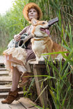 Redhead woman with guitar and corgi dog in countryside Stock Photos