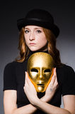Redhead woman in hat  iwith mask in hypocrisy consept. Against dark  grey background Royalty Free Stock Photo