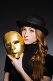 Redhead woman in hat  iwith mask in hypocrisy consept. Against dark  grey background Royalty Free Stock Image