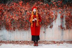 Free Redhead Woman Hol Flower In Red Coat On Autumn Background. Girl On Background Wall With Orange Autumn Leaves. Red Turban And Stock Images - 158348114