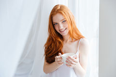 Redhead woman holding cup with tea at home Stock Images
