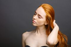 Redhead woman holding her healthy and shiny hair, studio grey. Beautiful redhead woman holding her healthy and shiny hair, studio gery Stock Photography