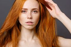 Redhead woman holding her healthy and shiny hair, studio grey. Beautiful redhead woman holding her healthy and shiny hair, studio gery Royalty Free Stock Photo