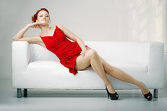 Free Redhead Woman In A Red Dress On White Couch Royalty Free Stock Photography - 21873997
