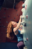 Redhead Woman Indoor Rock Climbing. Strong Heroic Female Climber Royalty Free Stock Images