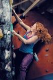 Redhead Woman Indoor Rock Climbing. Strong Heroic Female Freeclimbing Stock Photo