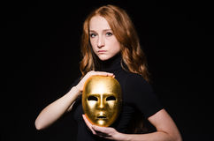 Redhead woman iwith mask. In hypocrisy consept against black  background Stock Photo