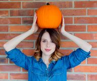 Redhead woman in jeans clothes holding orange autumn pumpkin. Portriat on brick background. Vagetable may be ECO product Royalty Free Stock Photos