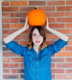 Redhead woman in jeans clothes holding orange autumn pumpkin. Portriat on brick background. Vagetable may be ECO product Royalty Free Stock Images