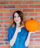Redhead woman in jeans clothes holding orange autumn pumpkin Stock Image