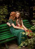 Redhead woman kissing brunette girl on bench at park Stock Images