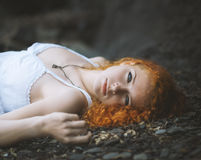 Redhead woman laid down on the gravel. Royalty Free Stock Photos