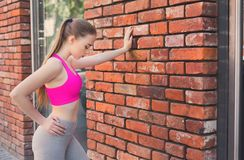Redhead woman leaning on brick wall. Pensive blonde woman leaning on brick wall, relaxing from jog training, copy space Stock Image