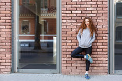Redhead woman leaning on brick wall Royalty Free Stock Photos