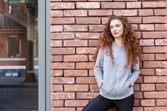 Redhead woman leaning on brick wall Stock Photography