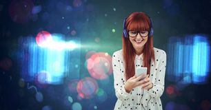 Redhead woman listening to music against abstract background Stock Images