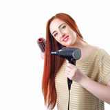 Redhead woman with long hair holding hair dryer and comb Stock Photo